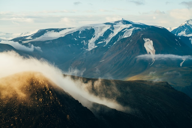 Paisagem alpina atmosférica com grande nuvem baixa dourada brilhante na rocha e gigantes montanhas nevadas com geleiras no nascer do sol. voando sobre montanhas acima das nuvens na hora de ouro. maravilhoso cenário das montanhas.