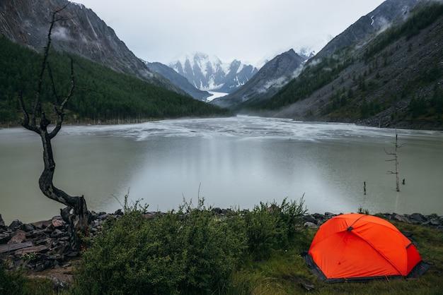 Paisagem alpina atmosférica com tenda laranja na margem do lago de montanha verde e montanhas nevadas em tempo chuvoso. cenário sombrio com círculos chuvosos na água do lago da montanha e nuvens baixas no vale