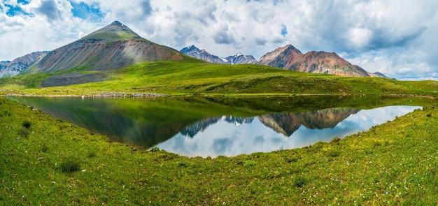 Paisagem alpina azul verde brilhante com lago de montanha no vale das montanhas na luz do sol e grande montanha sob o céu azul nublado. sombra de nuvens no vale verde da montanha. vistas panorâmicas.