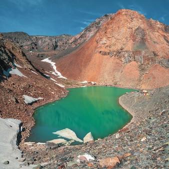 Paisagem alpina brilhante com lago de montanha no vale das terras altas na luz solar. acampamento de montanhismo no lago azul. aktru. vistas quadradas.