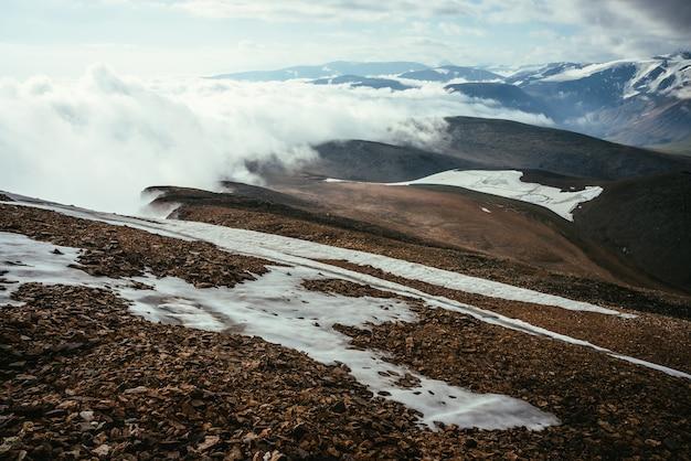 Paisagem alpina cênica com camadas de montanhas ao horizonte em densas nuvens baixas. maravilhoso relevo da montanha em camadas em nuvens nas terras altas. montanhas nevadas e geleiras em nuvens espessas em grande altitude