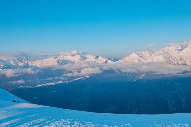 Paisagem alpina de montanhas cobertas de neve e céu azul