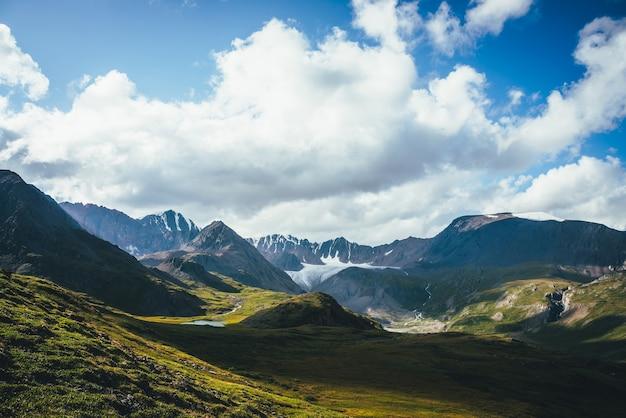 Paisagem alpina verde azul cênica com lago de montanha no vale das terras altas na luz do sol e grande geleira sob céu nublado. sombra de nuvens no vale verde da montanha. nuvens sombreadas em rochas e colinas.