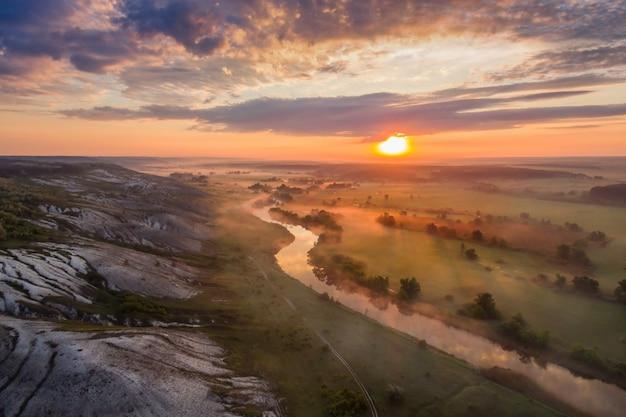 Paisagem ao nascer do sol com nevoeiro, rio e colinas calcárias