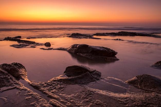 Paisagem ao nascer do sol na costa, com reflexão