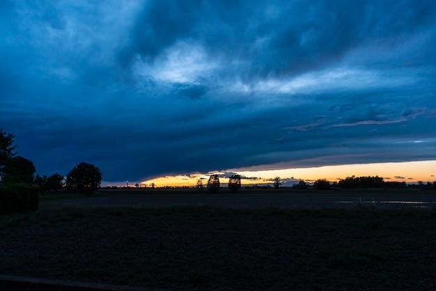 Paisagem ao pôr do sol com tempestade chegando na primavera
