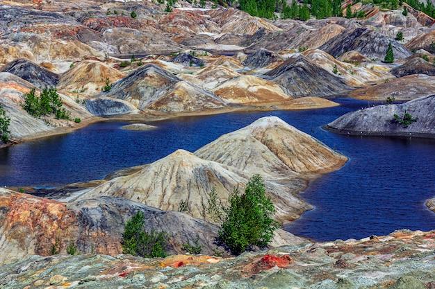 Paisagem apocalíptica como um planeta superfície de marte. vista fantástica do lago azul. superfície terrestre preta marrom-avermelhada solidificada. terra estéril, rachada e queimada. conceito de aquecimento global.