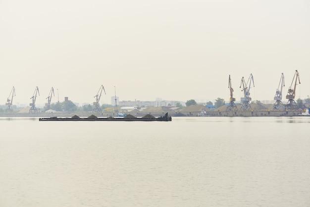 Paisagem aquática do rio industrial com barcaça de carga a granel e terminal de carga na neblina matinal