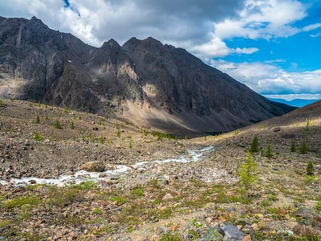 Paisagem atmosférica alpina ensolarada com riacho de montanha entre morenas em tempo ensolarado.