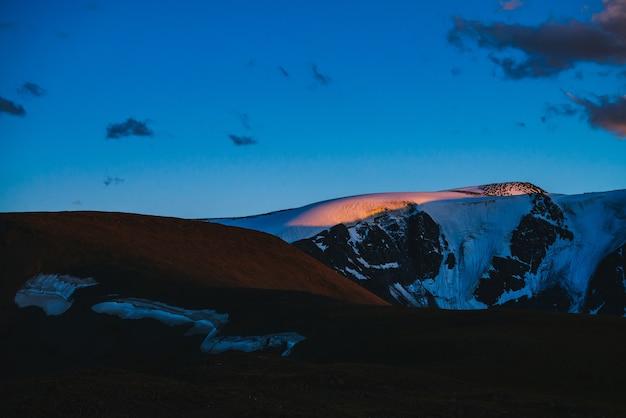Paisagem atmosférica ao amanhecer com silhuetas de montanhas nevadas e geleiras
