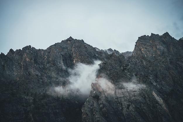 Paisagem atmosférica de montanha com nuvens baixas em rochas afiadas. montanha rochosa incrível com topo pontiagudo. rochas escuras em céu nublado. belas paisagens com nuvens baixas em penhascos ásperos. pináculo pontiagudo.