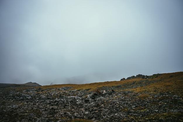 Paisagem atmosférica escura à beira do abismo nas terras altas. montanhas perigosas e abismo entre nuvens baixas. passagem de montanha de perigo e rochas afiadas nas nuvens. perigoso clima nublado e chuvoso nas montanhas.