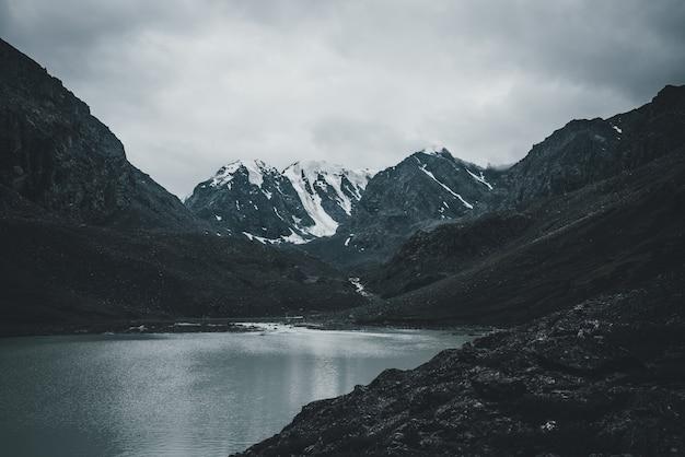 Paisagem atmosférica escura com lago de montanha entre rochas negras profundas no fundo das montanhas nevadas, sob um céu cinzento nublado. vista desolada para o lago de montanha e a geleira em cores pretas profundas. tons escuros.