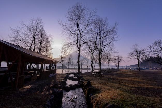 Paisagem azul céu fumoto para terra de acampamento e fuji montanha com reflexões de árvore