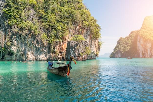 Paisagem bonita da montanha das rochas e do mar claro com o barco do longtail em phuket, tailândia.