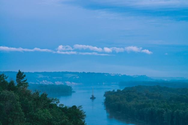 Paisagem bonita da noite do rio com costas e o navio verdes.