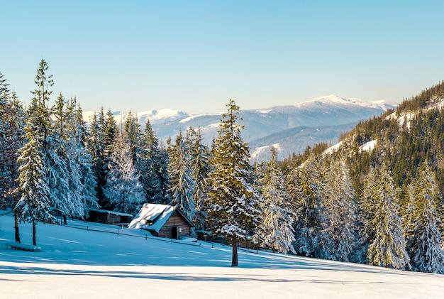 Paisagem bonita do inverno nas montanhas com caminho de neve nas estepes e pequena casinha.