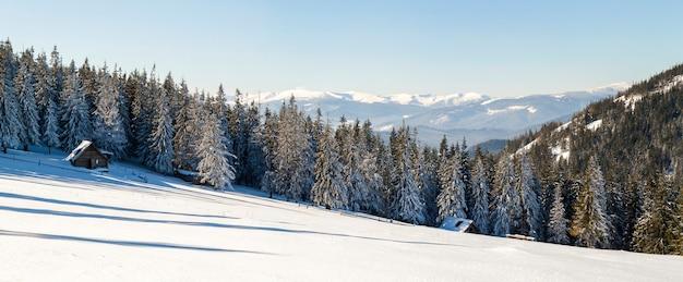 Paisagem bonita do inverno nas montanhas com caminho de neve nas estepes e pequena casinha