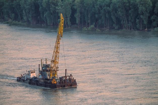 Paisagem bonita do rio com costas verdes e navio com espaço da cópia.