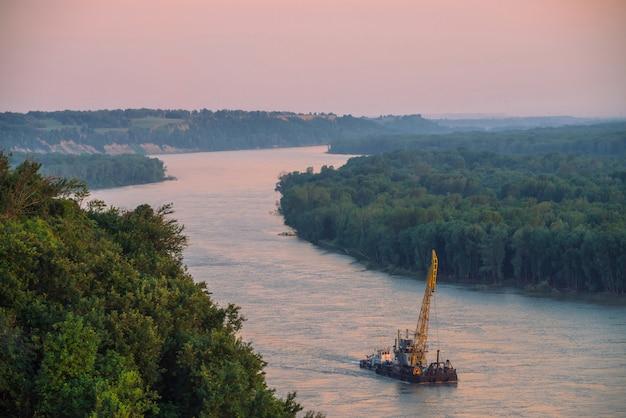 Paisagem bonita do rio com costas verdes e navio.