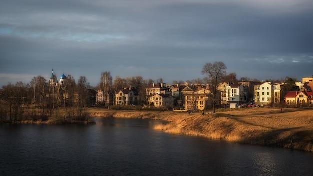 Paisagem brilhante primavera com casas perto de um lago à noite