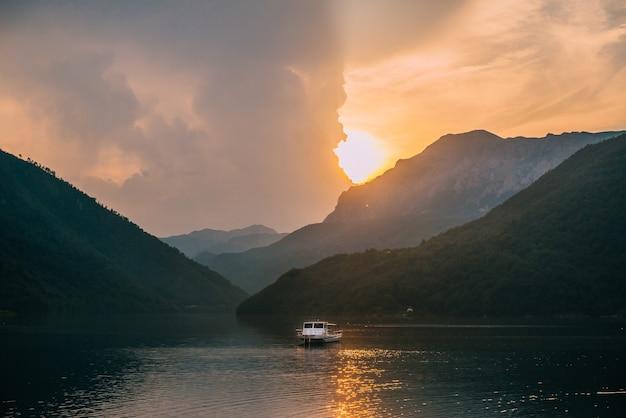 Paisagem calma com vista para um lago de montanha e um barco solitário durante o pôr do sol.