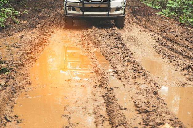 Paisagem campestre com carro na estrada enlameada