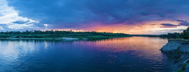 Paisagem campestre de um belo pôr do sol e nuvens sobre o rio