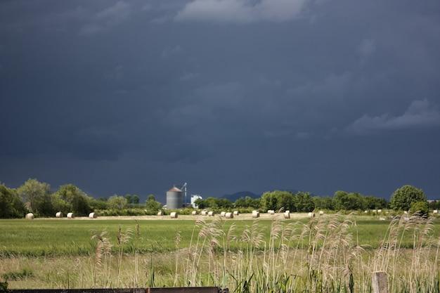 Paisagem campestre italiana durante a chegada de uma forte tempestade, com céu muito escuro e alto contraste com a natureza circundante.