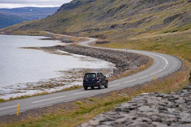 Paisagem cênica com carro dirigindo pela bela estrada, fiorde e litoral da islândia westfjord.