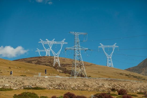 Paisagem colorida com a estrada bonita da montanha com estrutura elétrica de alta tensão do polo e céu azul.