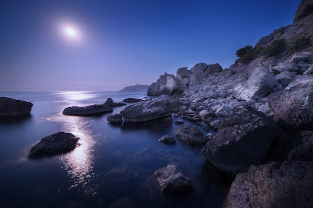 Paisagem colorida da noite com lua cheia, trajeto lunar e rochas no verão. paisagem montanhosa no mar