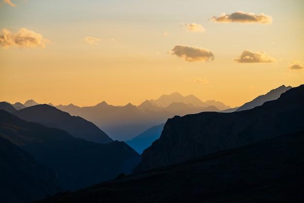 Paisagem colorida do amanhecer com belas silhuetas de montanhas azuis e céu gradiente dourado com nuvens. vivas paisagens montanhosas com pitoresco pôr do sol multicolor. vista panorâmica do nascer do sol para a cordilheira.
