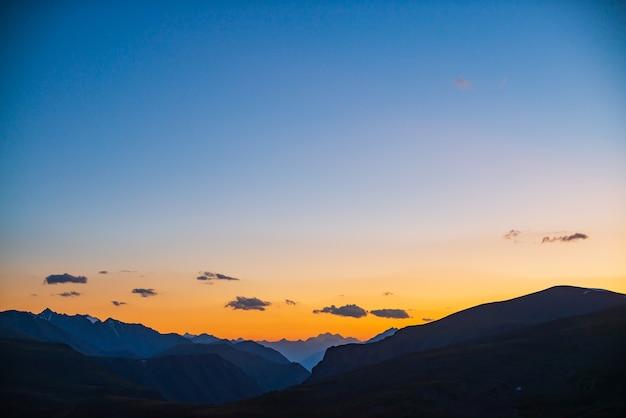 Paisagem colorida do amanhecer com belas silhuetas de montanhas e céu gradiente dourado