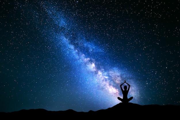 Paisagem com a via láctea azul. céu noturno com estrelas e a silhueta de uma garota praticando ioga na colina.