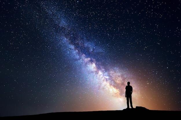 Paisagem com a via láctea. céu noturno com estrelas e a silhueta de um homem feliz em pé na montanha.