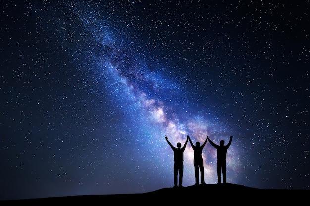 Paisagem com a via láctea colorida e a silhueta de uma família feliz com os braços erguidos na montanha. céu estrelado à noite. belo universo.