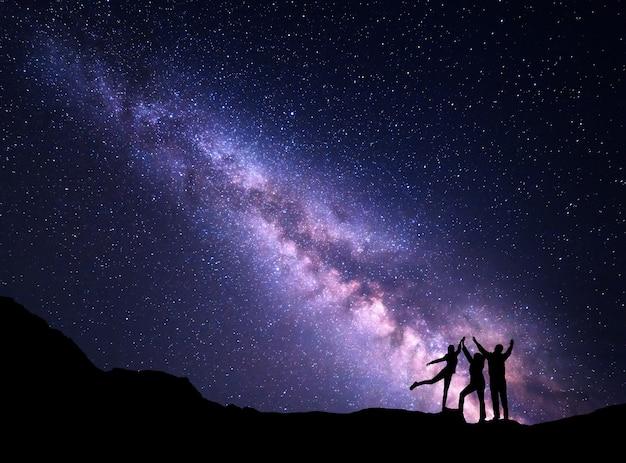 Paisagem com a via láctea roxa. céu estrelado à noite com a silhueta de uma família feliz com os braços erguidos na montanha.