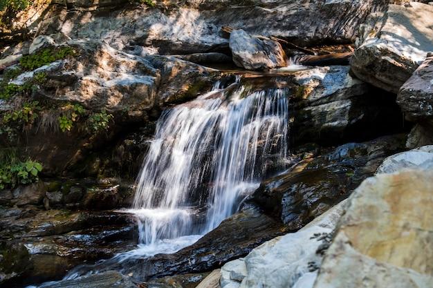 Paisagem com água corrente de cachoeira nas montanhas