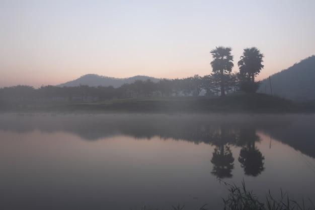 Paisagem com árvores de montanhas e um rio em frente ao amanhecer