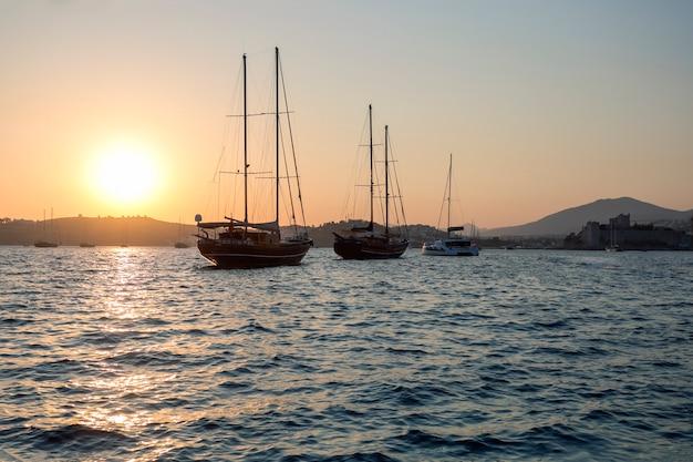 Paisagem com barcos à vela na baía da marina ao pôr do sol.