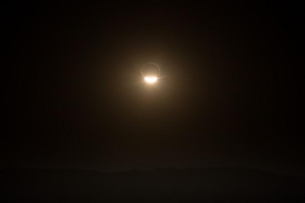 Paisagem com eclipse total de assim, sobre as montanhas