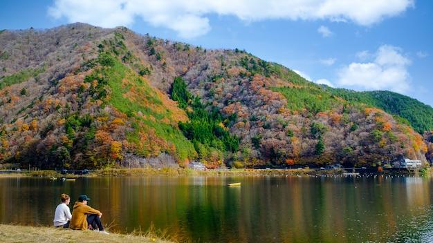 Paisagem com folhas de outono do lago kawaguchiko e casal sentado à beira do rio no japão
