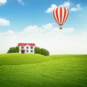 Paisagem com gramado com casa e balão de ar no céu