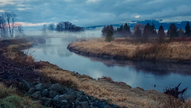 Paisagem com lago e nevoeiro Foto gratuita