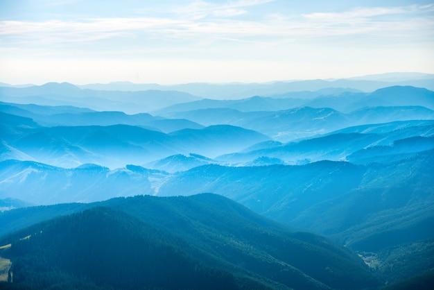 Paisagem com montanhas azuis, floresta e nuvens brancas no céu