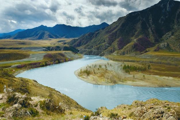 Paisagem com montanhas, floresta e um rio na frente.