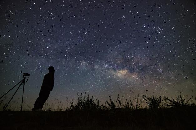 Paisagem com o céu noturno da via láctea com estrelas e a silhueta de um homem feliz em pé