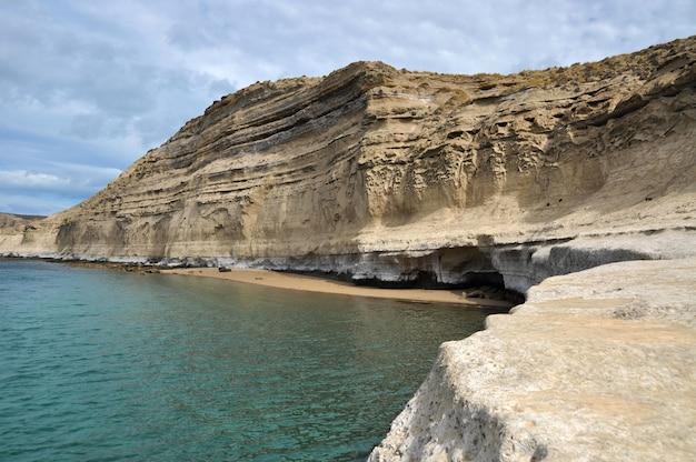 Paisagem com penhascos de calcário e uma pequena praia na península valdés, na patagônia