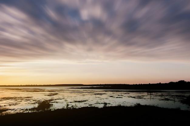 Paisagem com pôr do sol à beira mar